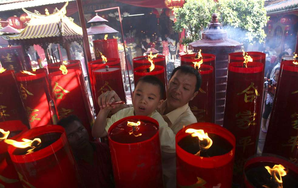An Indonesian ethnic Chinese man  carry his boy during Lunar New year celebration at a temple in Chinatown in  Tangerang, Banten province, Indonesia, Monday, Jan. 23, 2012.  (AP Photo/Achmad Ibrahim)